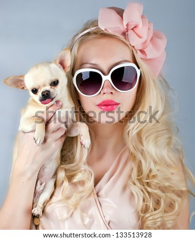 beautiful glamour woman in sunglasses with small dog in hands - stock photo