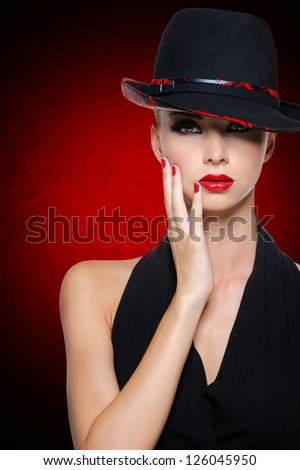 Beautiful glamour woman with bright sexy red lips dressed in black dress. Art background. - stock photo