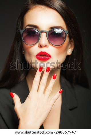 Beautiful glamour woman with fashion sunglasses, red lips and nails on dark background