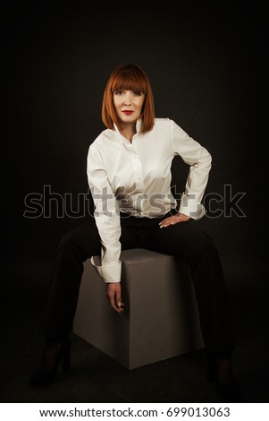 Beautiful glamour woman with perfect make up and hairstyle in studio photo. Beauty and fashion. Hairstyle and make up. A woman in the Studio sitting