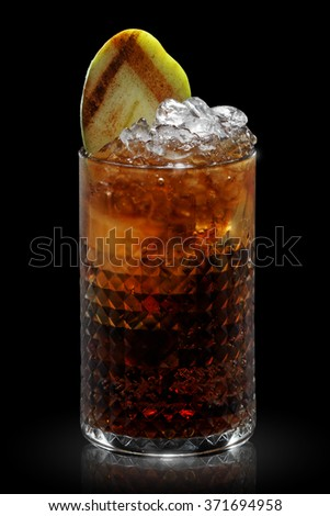 Beautiful glass with facets. Filled with a refreshing drink. Alcoholic cocktail on a black background. Cold drink with ice.