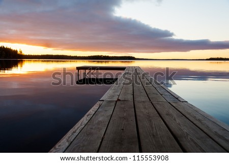 Beautiful glowing orange sunset over a rustic timber plank jetty reflected in the mirror calm waters of the lake below, a background of natural beauty and serenity - stock photo