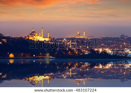 Beautiful glowing sunset in Istanbul, Turkey. Cityscape with street lights and mosques reflected in peaceful Bosphorus