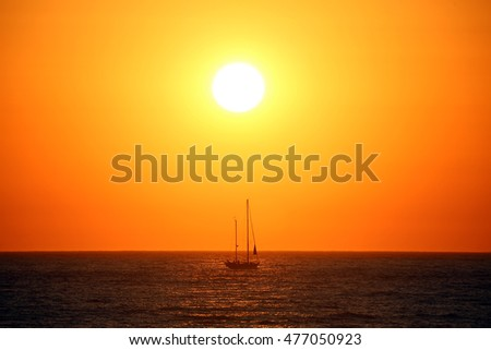 Beautiful gold and orange sundown with a sailboat sailing on a calm sea