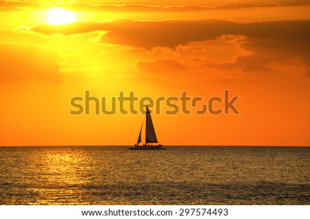 Beautiful gold and orange sunset with a sailboat sailing through the beam of sunlight