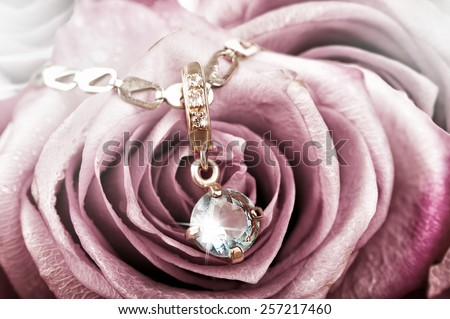 Beautiful gold pendant with big blue topaz and diamonds on rose petals - stock photo