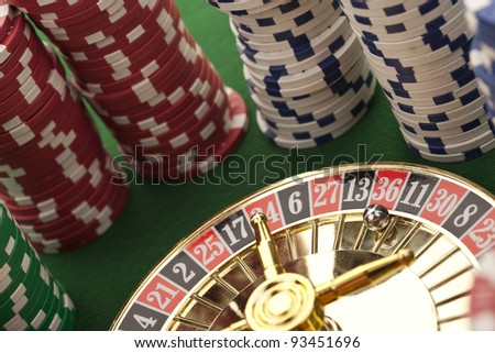 Beautiful gold roulette with casino chips on a green background.