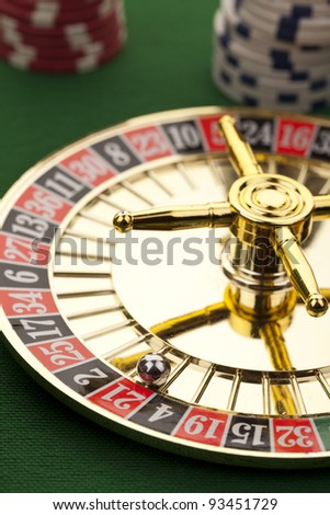 Beautiful gold roulette with casino chips on a green background. - stock photo