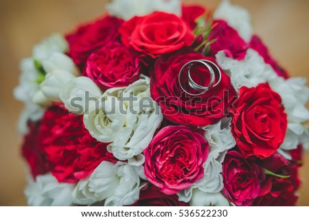 beautiful gold wedding rings lying on bouquet of flowers