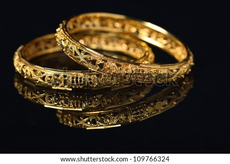 Beautiful golden bangles isolated on black backround - stock photo
