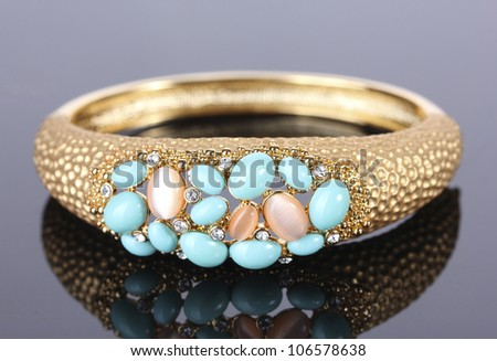Beautiful golden bracelet with precious stones on grey background