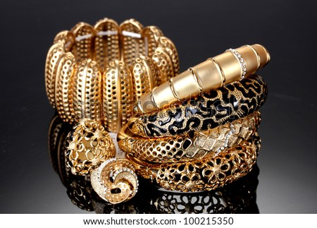 Beautiful golden bracelets and rings on grey background - stock photo