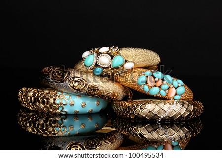 Beautiful golden bracelets isolated on black background - stock photo