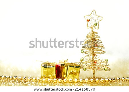 Beautiful golden decorative christmas tree and gifts on golden glitter background with white copy space