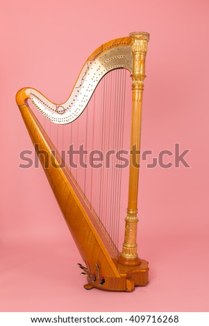 beautiful golden harp on a pink background - stock photo