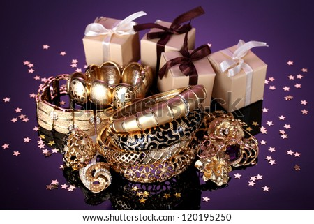 Beautiful golden jewelry and gifts on purple background - stock photo