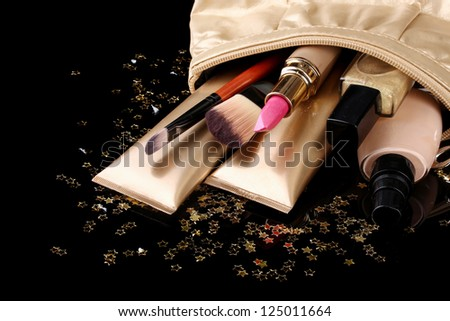 Beautiful golden makeup bag and cosmetics isolated on black - stock photo