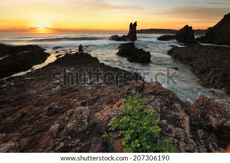 Beautiful golden orange sunrise colours cast over the landscape at Cathedral Rock, Kiama Australia.   These volcanic rocks have lured many tourists and photographers due to their distinctive shapes. - stock photo