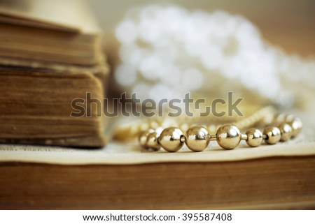 Beautiful golden pearls necklace closeup on a vintage book background - stock photo