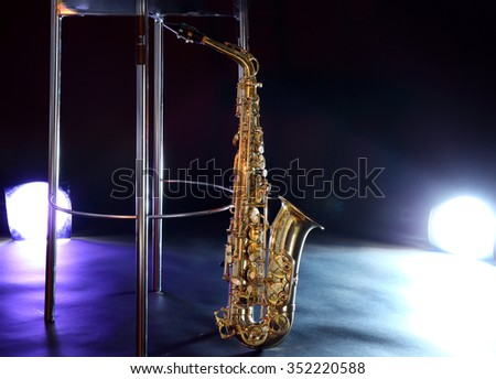 Beautiful golden saxophone near bar stool on a scene - stock photo
