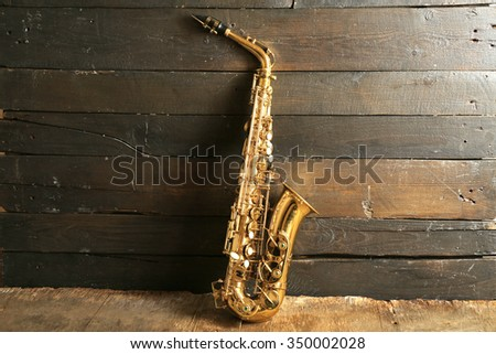 Beautiful golden saxophone on wooden background - stock photo