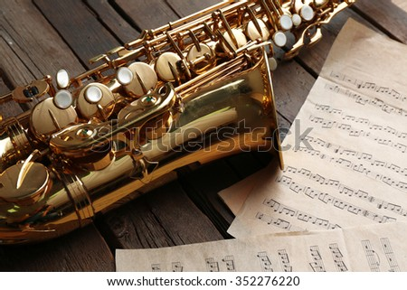 Beautiful golden saxophone with musical notes on wooden background, close up