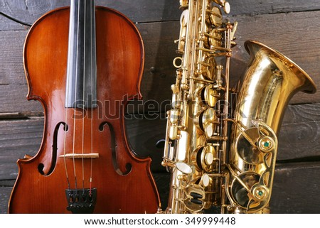 Beautiful golden saxophone with violin on wooden background, close up
