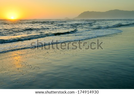 Beautiful golden sunset above the ocean and sandy beach - stock photo