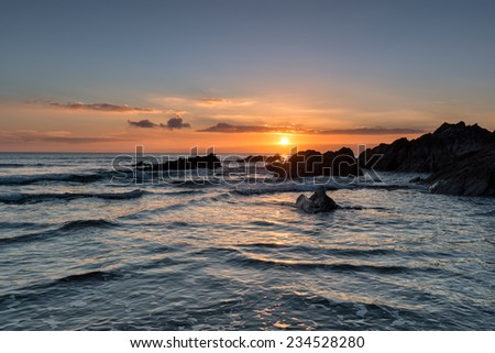 Beautiful golden sunset over rocks at Freathy beach in Whitsand Bay in Cornwall
