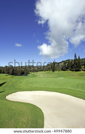 Beautiful Golf Course Fairway with White Sand Bunker, Blue Sky and Dramatic Fluffy Clouds