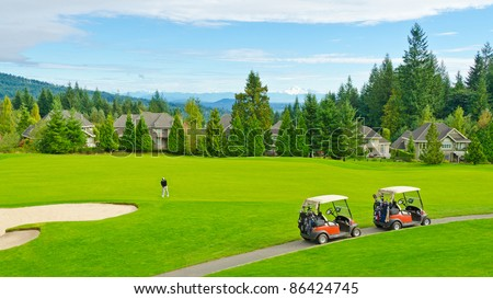 Beautiful golf place with gorgeous green and fantastic snow mountain view over blue sky with white clouds. - stock photo