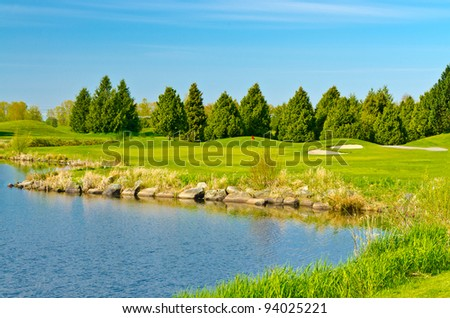 Beautiful golf place with gorgeous green, pond in winter - stock photo