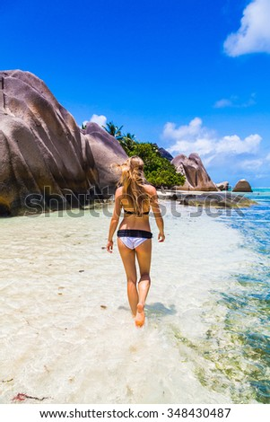 Beautiful gorgeous girl in a white swimming suit walking down the paradise beach in the shallow water on Seychelles