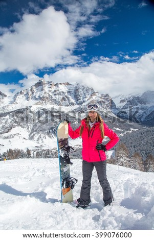 Beautiful gorgeous girl standing on the mountain next to the snowboard - stock photo