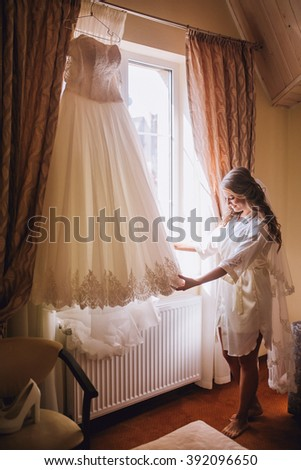 beautiful gorgeous stylish bride getting ready in the morning in the room - stock photo