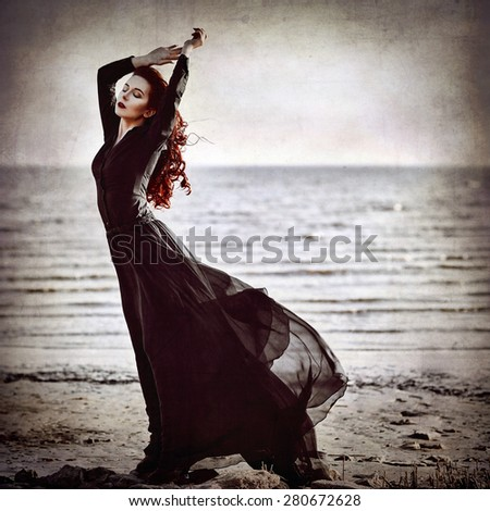Beautiful goth girl standing on the sea coast. Grunge texture effect
