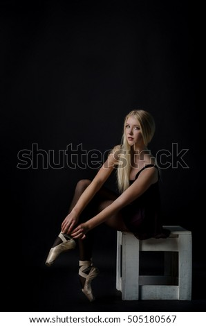 Beautiful graceful blond dancer in bright satin pointe shoes. Delicate, fragile girl.
