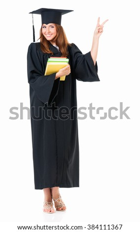Beautiful graduate girl student in mantle with books showing victory sign, isolated on white background