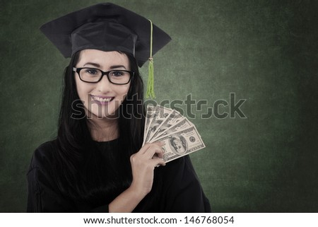 Beautiful graduate student get money as a gift - stock photo