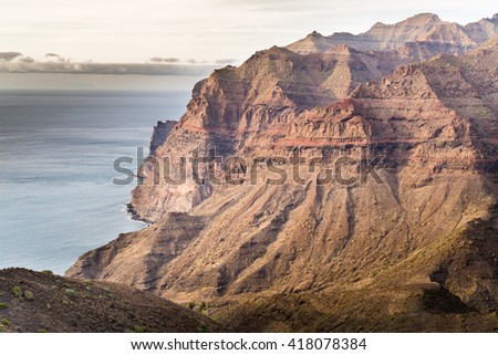 BEAUTIFUL GRAN CANARY MOUNTAINOUS LANDSCAPE WITH CLOUD AND DRAMATIC SKY AND CACTUS IN FOREGROUND - stock photo