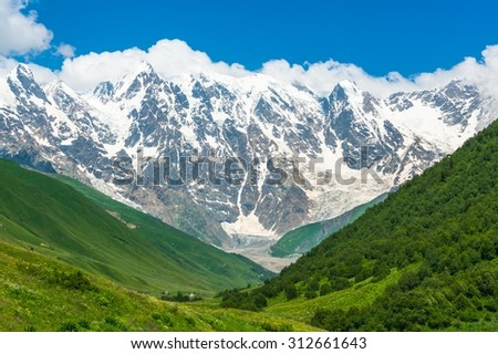 Beautiful grassy valley and snow-capped mountains in Georgia (Svaneti)