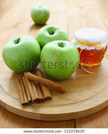 Beautiful green apples, flavored honey in a pot and cinnamon.