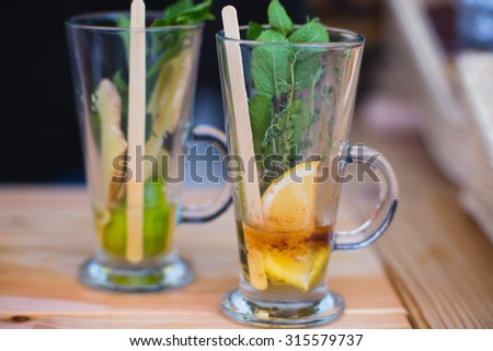 Beautiful green black tea drink with lemon, cinnamon, mint, thyme and ginger, beautiful coloured alcohol cocktail on corporate party event, catering, near bar, on a banquet, buffet