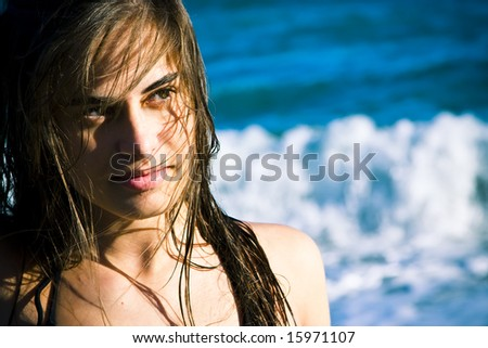 Beautiful green eyed woman portrait with the sea as background. - stock photo