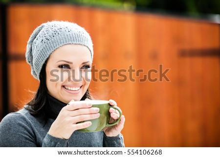 Beautiful green eyed young woman in warm clothes and gray hat smiling, drinking tea in a big cup outdoors in autumn time