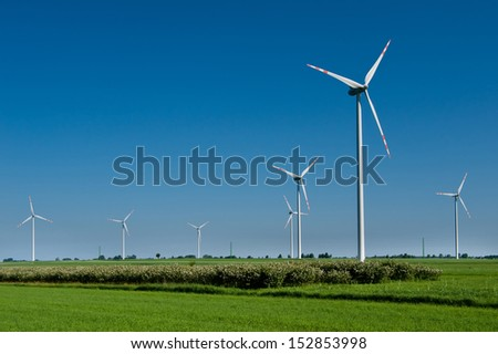 Beautiful green field with wind turbines generating electricity - stock photo