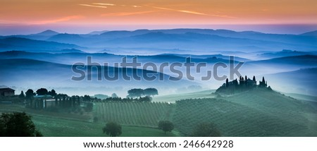 Beautiful green fields and meadows at sunset in Tuscany - stock photo