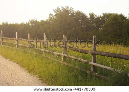 Beautiful green grass meadow with wooden fence. Colorful scenic background. - stock photo