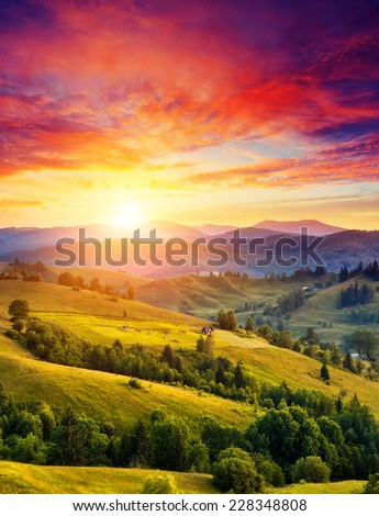 Beautiful green hills glowing by sunlight at twilight. Dramatic scene. Colorful sky. Carpathian, Ukraine, Europe. Beauty world. - stock photo