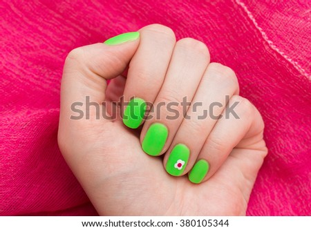 beautiful green nails on a red background - stock photo